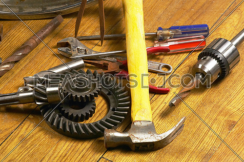 bounch of rusty tools and gears on the wood floor