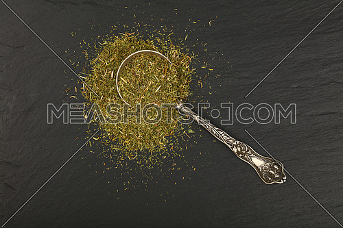 Close up one vintage antique metal spoon full of green dried herbs, dill or marjoram on background of black slate board, elevated top view, directly above