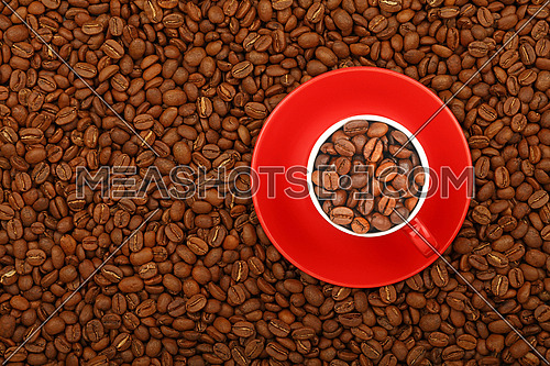 Arabica coffee beans in full red cup with saucer on background of roasted coffee beans, elevated top view, close up