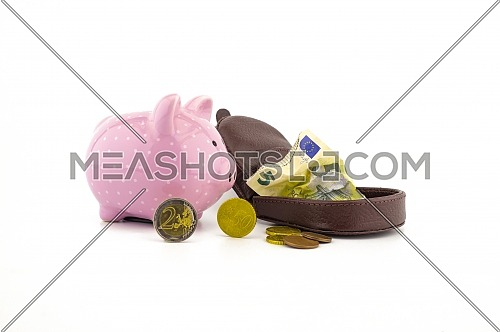 Open leather purse with crumpled banknotes, coins and cute pink piggy bank on white with copyspace for financial or savings concepts