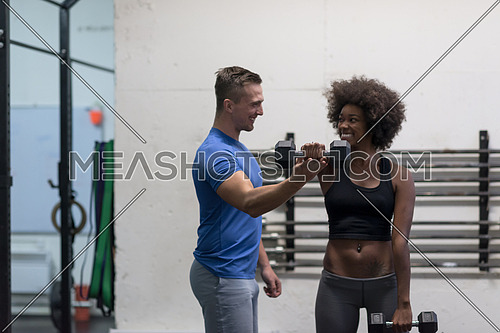 young beautiful African American woman doing bicep curls with fitness trainer in a gym