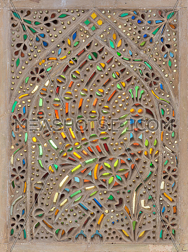 Perforated stucco window decorated with colorful stain glass with geometrical circular patterns, one of the traditions of the Ottoman era, Museum of Islamic Art, Cairo, Egypt
