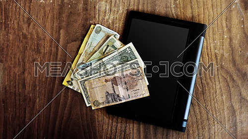 different currencies on wooden background and tablet