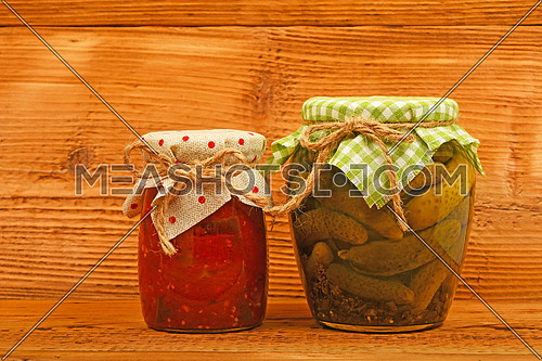 One glass jar of homemade pickled cucumbers with green checkered textile top decoration and eggplant salad at unpainted vintage wooden surface