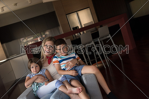 portrait of  a happy Mother with kids on an armchair  at home