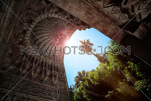 A low angle show showing and arch with islamic architecture and the sun flaring