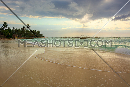 A nice beach with Several fishing boats anchored at sunset with sunbeams.Zanzibar coast,Tanzania.