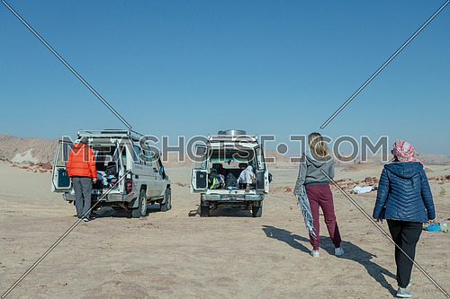 Group of tourists and cars gettig rest on sands with bedouin guide while exploring Sinai Trail from Ain Hodouda at day.