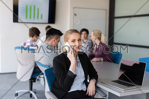young business woman speaking on phone at modern startup office interior, team in meeting group in background