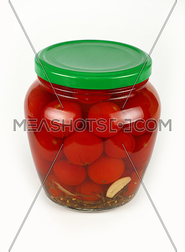 Close up of one glass jar of pickled small red cherry tomatoes with green lid over white background, high angle view