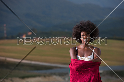 Outdoor portrait of young beautiful black woman with red scarf around shoulder