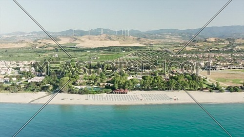 Aerial view of beautiful sea and beach with parasol at sunny day, seascape and hill mountain on backgrond, Simeri Mare, Calabria, Southern Italy