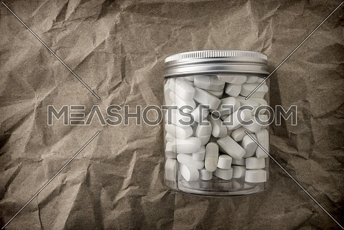 Bottle of white tablets on crumpled paper background, conceptual image