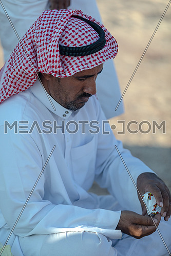 Portirat for a bediuon male wearing traditional clothing and smoke cigarettes in Sinai by day.
