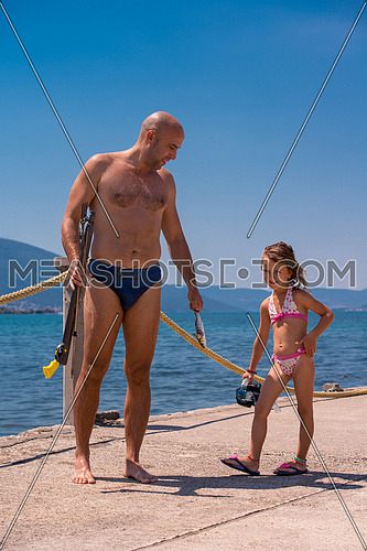 Young smiling fisherman with his little daughter carrying freshly caught fish after underwater fishing  active holiday concept