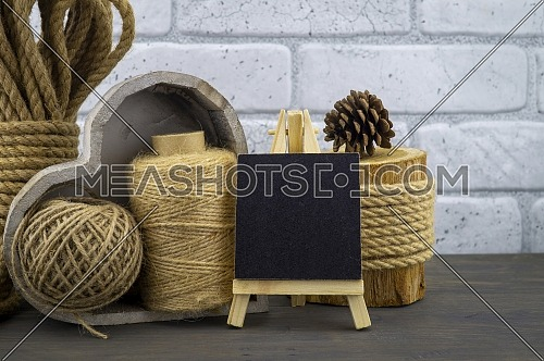 Assorted balls of hemp twine and string with skeins of rope and slate chalkboard in a close up rustic still life