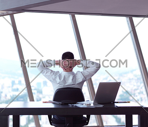 happy young business man work and relax at modern bright office interior, hipster with beard at workplace