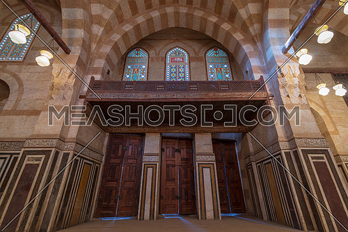 Marble wall with three wooden doors, huge arches and stained glass windows at mosque attached to Khayer Bek Mausoleum, Darb Al-Ahmar district, Old Cairo, Egypt