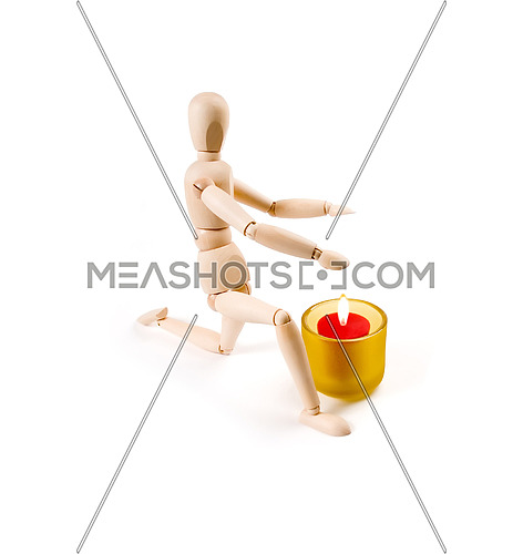 wood mannequin near a candle on white background