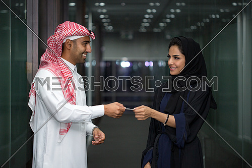 Saudi man and woman Taking business card after the meeting.