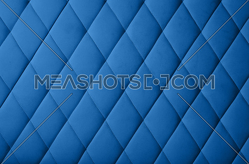 Close up background texture of dark blue genuine leather soft tufted furniture or classic wall panel upholstery with deep diamond pattern