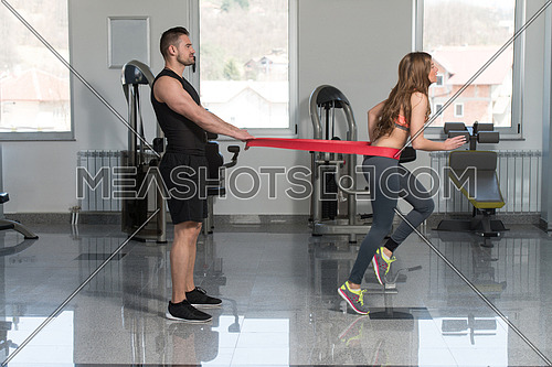 Young Couple Train Together With Resistance Bands A Leg Exercise In A Health And Fitness Concept
