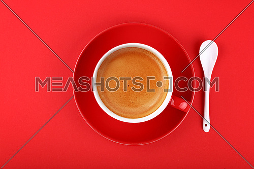 Close up one full cup of espresso coffee and saucer with white spoon over vivid red paper background, elevated top view, directly above