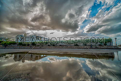 clouds and sky reflected on a water puddle in the street