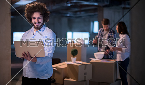 young male architect on construction site checking documents and business workflow using laptop computer with colleagues in the background in new startup office