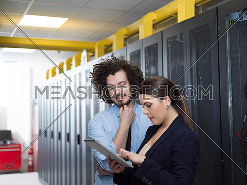 Young IT engineer showing working data center server room to female chief engineer who holding tablet computer