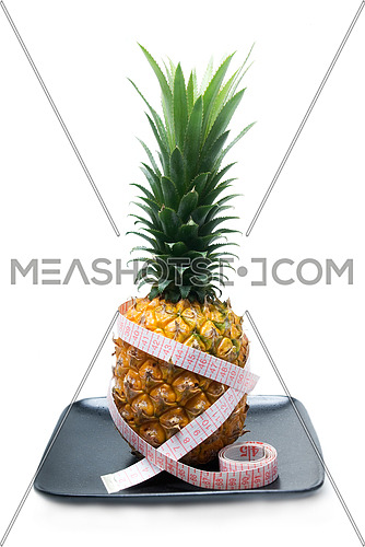 pineapple on a black plate with tape meter isolated on white background