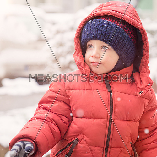 Infant boy while snowing looks towards the emptiness,covered with red winter jacket and woolen hat, close-up.