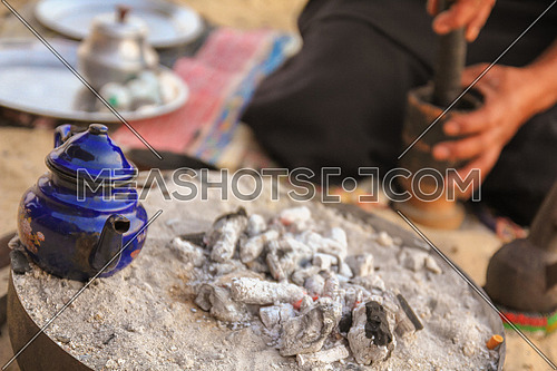Gringing traditional Gabana Coffee and a kettle of tea on charcoal