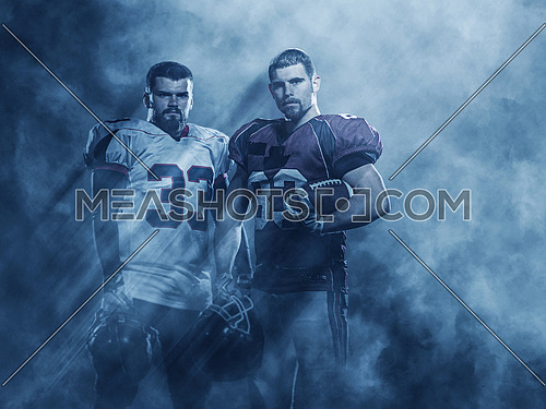 portrait of confident American football players holding ball while standing on the field with lights and smoke aroung