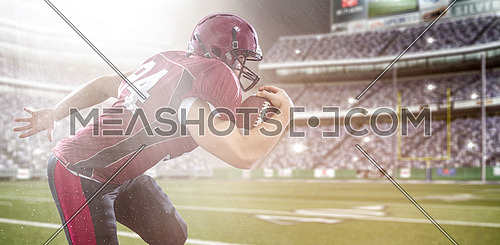 American football Player running with the ball isolated on big modern stadium field with lights and flares