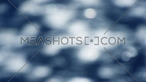 Abstract blur background of colorful blue bokeh glitter of defocused water ripples, fast running horizontally, close up, slow motion