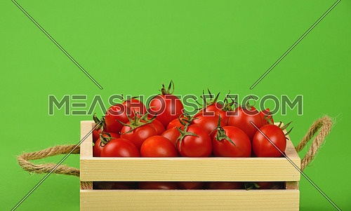 Red ripe fresh cherry tomatoes in small wooden box with twine jute handles on green paper background