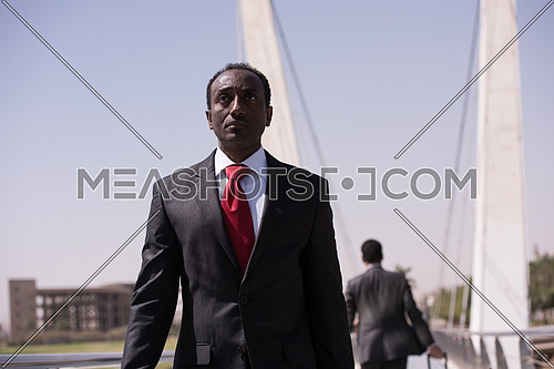 african businessman walking across modern bridge
