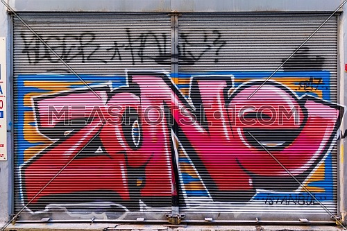 Istanbul, Turkey - April 18, 2017: Closed shop exterior with metal door covered with colorful graffiti at Hoca Tahsin Street, Karakoy district, Istanbul, Turkey