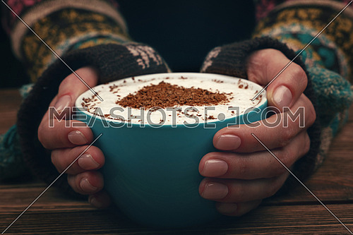 Close up two woman hands hold and hug big full cup of latte cappuccino coffee with heart shaped chocolate on milk froth over brown wooden table, low angle view