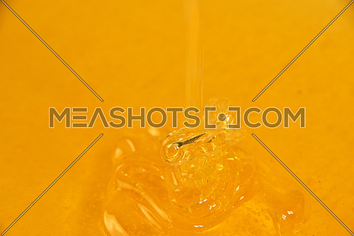 Close up background of pouring fresh thick fluid acacia honey in bowl, high angle view