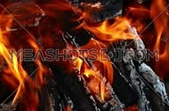 Blaze of bonfire, wood fire flame heat spires burning in fireplace with smoke and trembling in the wind and hot air flow, close up