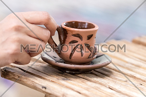 Holding a pottery oriental cup
