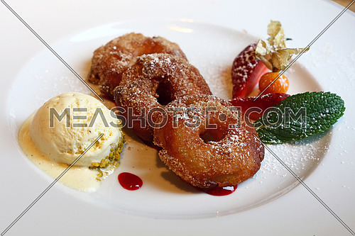 Close up portion of deep fried battered sweet apple rings with fresh ice cream and berries on white plate, traditional dessert of Bavarian German cuisine, high angle view