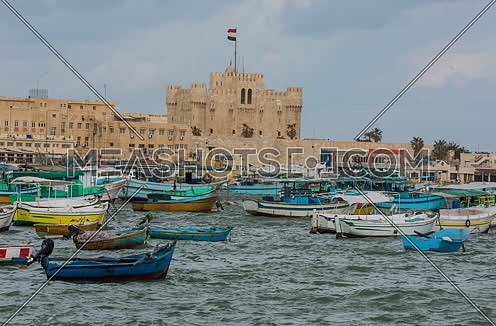 Track Right Long Shot outside Citadel of Qaitbay shows fishing boats at day
