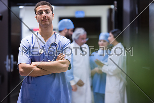 portrait of middle eastern team of doctors in a large modern clinic, one in front of the other