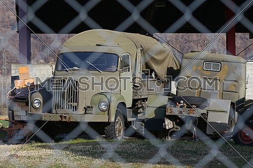 Old military transport truck behind a chain link fence at an army depot