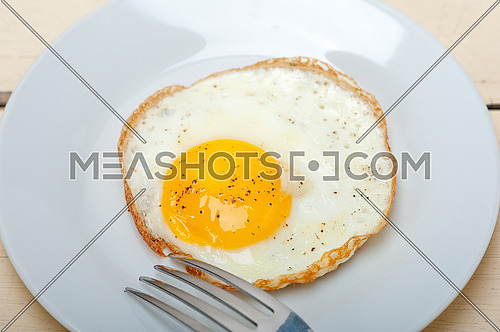 fried egg sunny side up on a plate with fork over wood table
