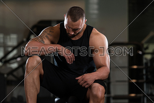 Beard Bodybuilder Resting At The Bench In A Gym