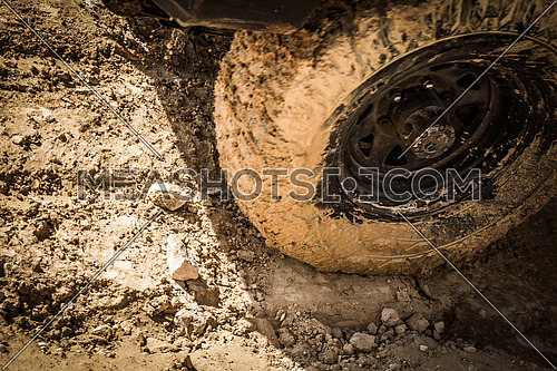 Wheels of a racing car spinning  on a Mud track